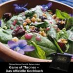 Salat mit Blüten in einer Holzschale; unten Werbung für das offizielle Kochbuch zu Game of Thrones