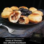 Krapfen mit Apfelfüllung auf einem Teller, in der Mitte Dörrpflaumen, im Vordergrund eine Gabel; unten ist Werbung für das offizielle Kochbuch zu Game of Thrones
