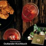 2 Gläser gefüllt mit Erdbeer-Limonade, daneben ein Teller mit Salat; unten Werbung für das offizielle Outlander-Kochbuch