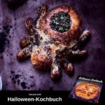 Brot in Form einer Spinne, mit schwarzem Sesam bestreut, das Hinterteil ist ausgehöhlt und mit einem dunklen Brei und frischen Kräutern gefüllt. Unten im Bild ist Werbung für das Halloween-Kochbuch.