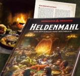 Cover von Heldenmahl, dem offiziellen Kochbuch zu Dungeons & Dragons; ein gezeichnetes Bild einer fantasy-Abeneteuergruppe an einem runden Tisch im Wirtshaus; im Hintergrund ein Bild von einer Rezeptseite aus dem Buch