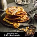 7 Pfannkuchen auf einem Stahltablett, der oberste ist angeschnitten, ein kleines Messer liegt daneben; unten Werbung für Heldenmahl, das offizielle Dungeons & Dragons Kochbuch