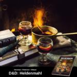 Glühwein in zwei Gläsern, mehr Glühwein in einem kleinen Topf und 3 Bücher auf einem Tisch; unten Werbung für Heldenmahl, das offizielle Dungeons & Dragons Kochbuch